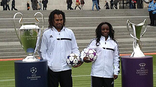 Christian Karembeu and Eniola Aluko with the UEFA Champions League and UEFA Women's Champions League trophies