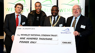 Wembley Managing Director Roger Maslin presents WNST Chairman Lord Toby Harris with a check for £900,000