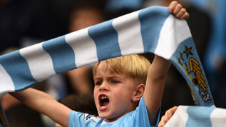 A Manchester City fan cheers on his team
